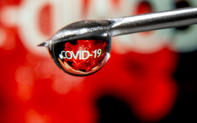 """The word """"COVID-19"""" is reflected in a vaccine drop that dangles from a syringe needle in this illustration photo Nov. 9, 2020."""