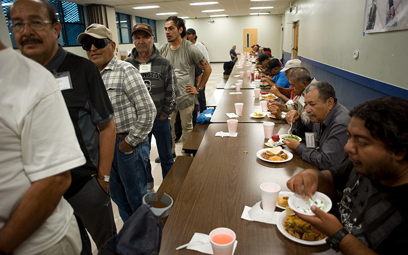 Men eat while others wait in line Sept. 7, 2018, at Dolores Mission Church in Los Angeles.