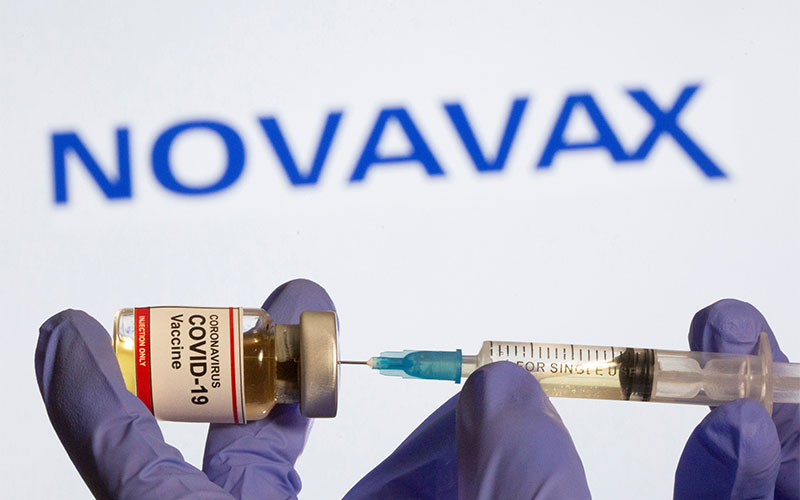"""A small bottle labeled with a """"Coronavirus COVID-19 Vaccine"""" sticker and a medical syringe is displayed in front of a Novavax logo in this illustration taken Oct. 30, 2020."""