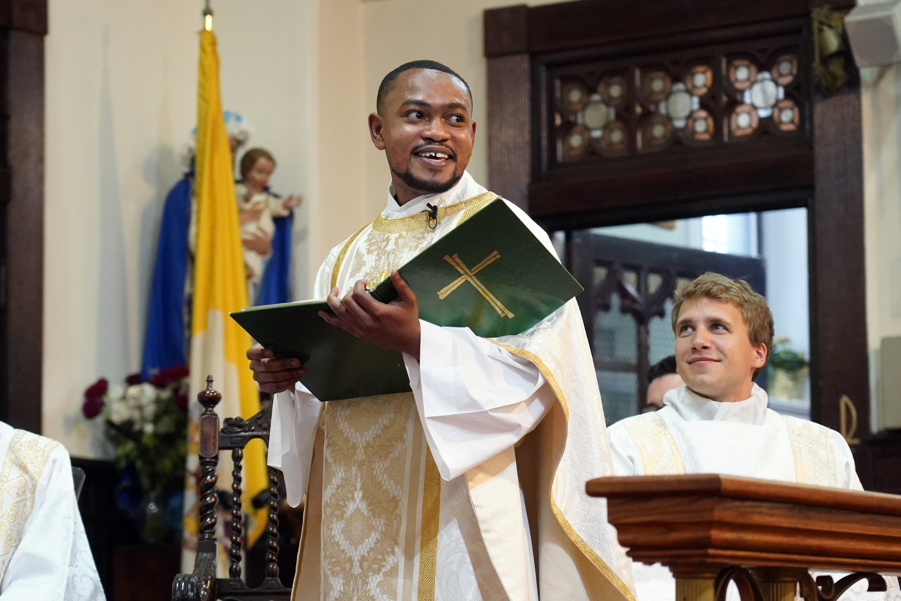 Father Wesbee Victor smiles as he celebrates his first Mass as a priest May 29, 2021, at St. Catherine of Genoa Church in New York City.