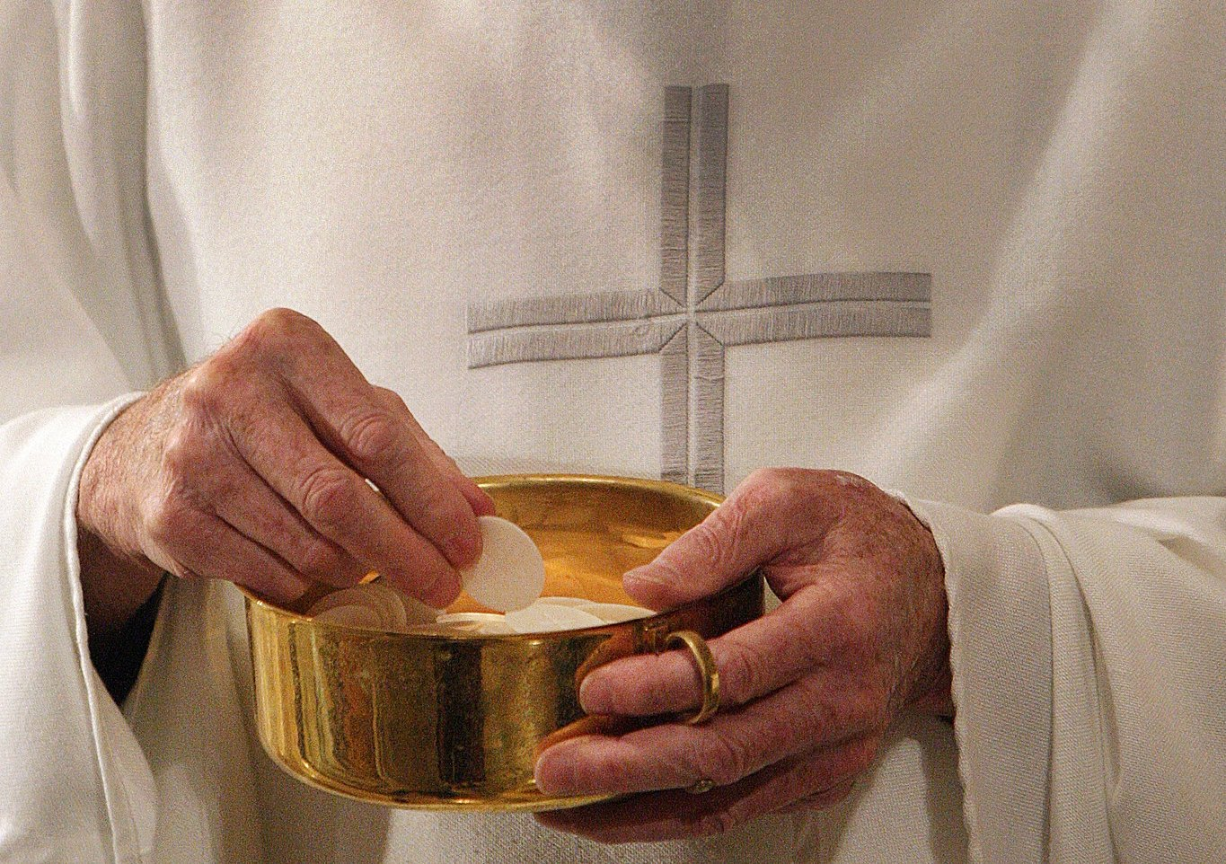 A priest prepares to distribute Communion during Mass in Washington.