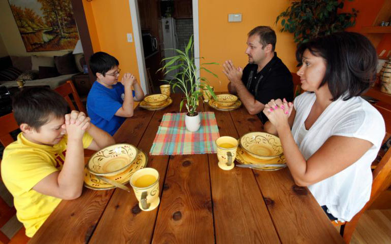 A family prays together before a meal in 2012 at their Chicago home.