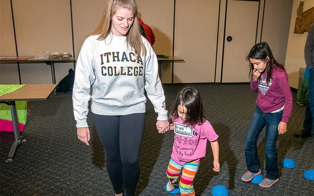 <p>Ithaca College student Julia Sideri of Long Island helps Caroline Vajk during the Play &lsquo;n Talk program at the Tompkins County Public Library in Ithaca Dec. 3.  </p>