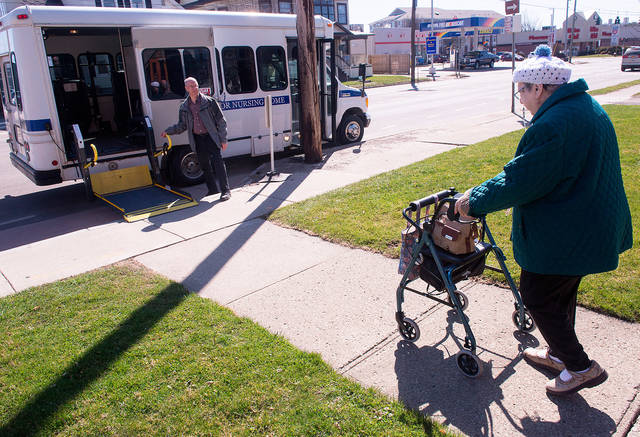 <p>The Sunday Bus picks up shut-ins and nursing-home residents each Sunday morning and transports them to services at churches in the Village of Penn Yan. Above, Rosie Weller leaves Mass at St. Michael Church April 22 as Fred Proietti waits to help her board the bus. (Courier photo by John Haeger) </p>
