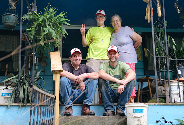 Church of the Transfiguration parishioners John Conley (front left) and Joey Campagna join Corey Checho (top left) in helping a needy resident of Booneville, Ky., with home repairs during a 2014 mission trip.