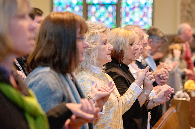 Patricia Carroll prays the Lord's Prayer alongside family members during the 100th-anniversary Mass for Rochester's St. John the Evangelist Church, which is now part of Peace of Christ Parish.