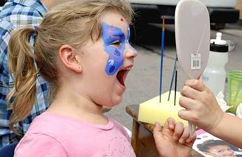 Five-year-old Shannon Bennett takes a look at her newly painted face during Guardian Angels' 50th-anniversary picnic June 27.