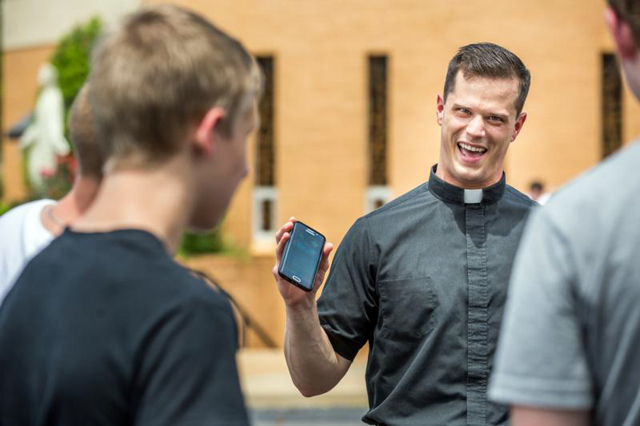 Father David Miloscia of Assumption Parish in St. Louis shows young people the game Pokemon Go on his cellphone as they chase Pokemon stops around the church grounds July 14.