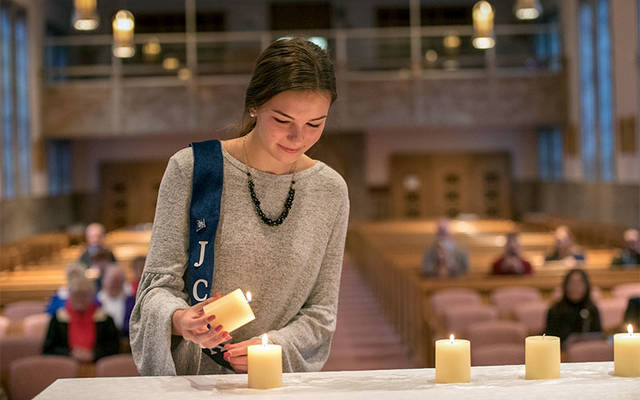 <p>Anika Fischer, president of Junior Catholic Daughters of the Americas Court Catherine McAuley No. 931, lights a candle during the installation of new officers at Our Lady of Mercy School for Young Women in Brighton Nov. 3. (Photo by Greg Francis) </p>