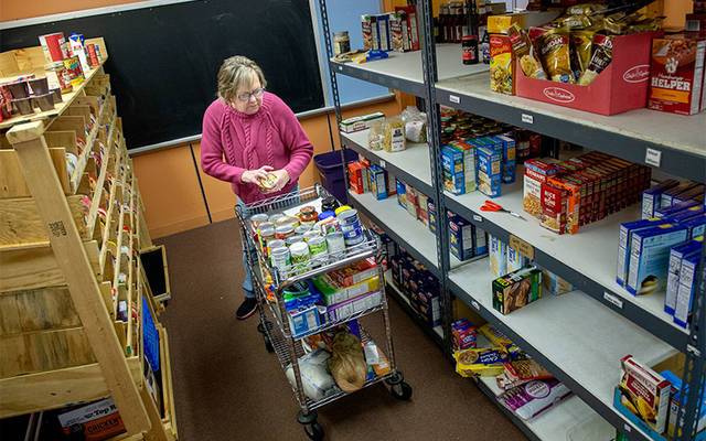 <p>Volunteer Mary O&rsquo;Grady-Pero pulls items from shelves at the Spencerport Ecumenical Food Shelf Nov. 29. (Courier photo by Jeff Witherow)  </p>
