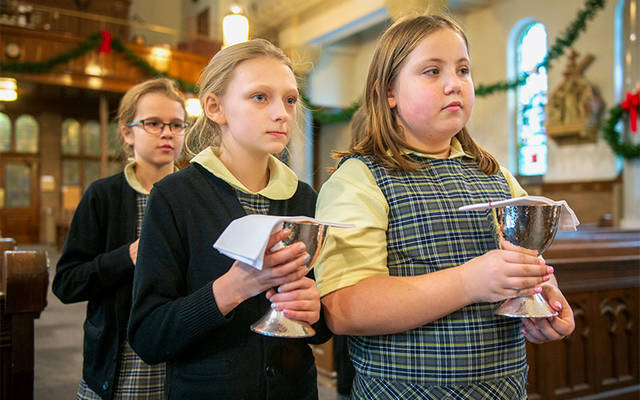 <p>Fourth-graders Maeve Jankowski (from left), Noelle Lewis and Leiliah Garrett carry the gifts during a Jan. 11 Mass at St. Mary Church in Canandaigua. (Courier photo by Jeff Witherow)  </p>