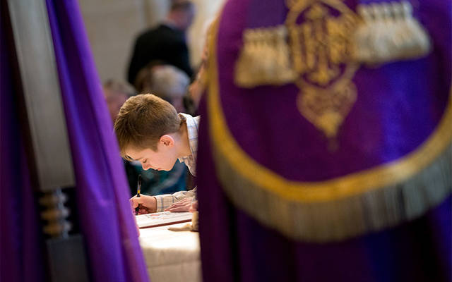 <p>Catechumen Nick Lepiane signs the Book of Enrollment during the Rite of Election and Call to Continuing Conversion at Rochester's Sacred Heart Cathedral March 5, 2017. (Courier photo by Jeff Witherow)