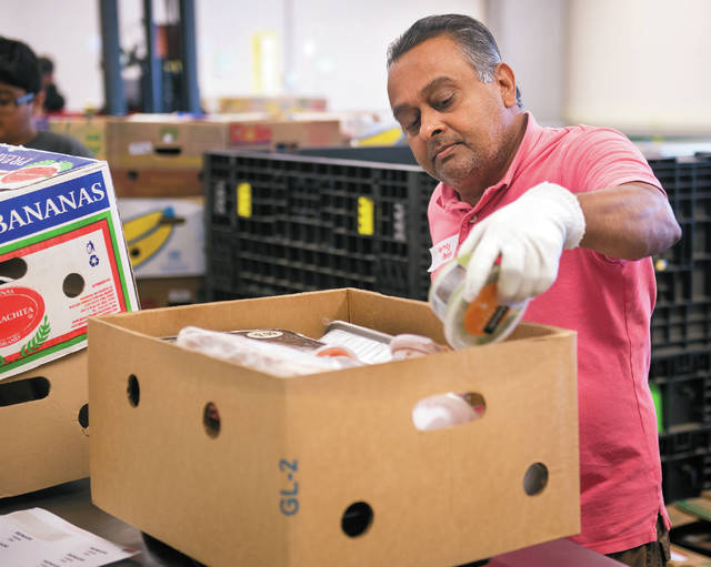 Volunteer Pankaj Patel boxes up meats at the Food Bank of the Southern Tier to be shipped to food pantries on July 20.