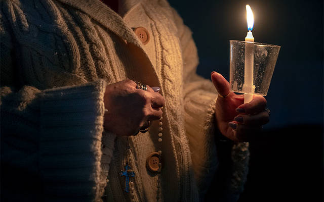<p>Mesina Pacete prays during a candlelit Living Rosary at St. Charles Borromeo Church in Elmira Heights March 14. (Courier photo by Jeff Witherow)  </p>