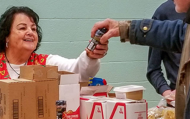 <p>Volunteer Bev Mello passes out spices March 2 during a monthly, Saturday-morning mobile food-truck distribution at St. Mary of the Lake Church in Watkins Glen. (Courier photo by Mike Latona)  </p>