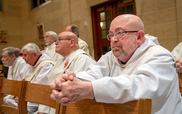 Deacon David LaFortune kneels during the Chrism Mass at Rochester's Sacred Heart Cathedral April 16. Deacon LaFortune is concluding his service as pastoral administrator of St. John Vianney Parish in Bath and Hammondsport at the end of June. (Courier photo by Jeff Witherow)