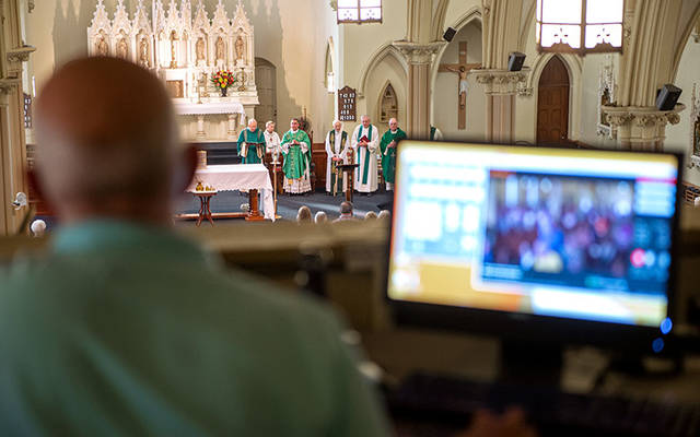 <p>Video operator Mike Paulin looks over the camera feed during a Sept. 15, 2018, Mass at St. Mary Church in Corning. (File photo)  </p>