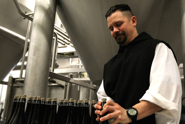Trappist Brother Jonah Pociadlo secures the cork to a bottle of Spencer Trappist Ale April 29 at the new state-of-the-art brewery on the grounds of St. Joseph's Abbey in Spencer, Mass. The monks began operating the first American Trappist brewery about a year ago.
