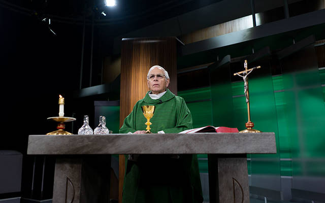 <p>Father Thomas Mull, pastor of Our Lady of Peace Parish in Geneva, celebrates Mass at WHEC studios in Rochester June 25. (Photo courtesy of WHEC-TV)  </p>