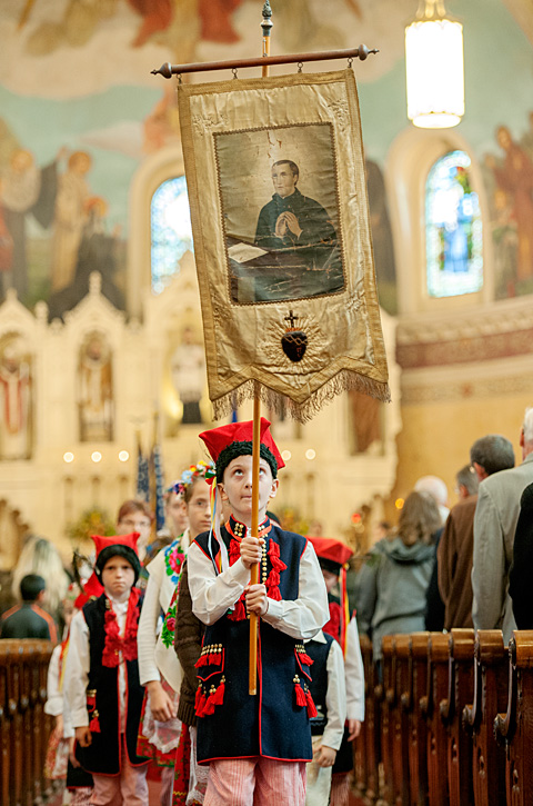 Stanis?aw Wojciechowski, 11, holds a banner with an image of St. Stanislaus during the Nov. 1 Mass marking the 125th anniversary of Rochester's St. Stanislaus Kostka Parish.