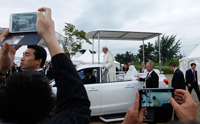 People take photos as Pope Francis leaves after celebrating the closing Mass of the sixth Asian Youth Day at Haemi Castle in Haemi, South Korea, Aug. 17.