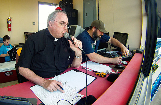 Father Craig Collison, a priest in the Diocese of Sioux City, Iowa, reads off his list of players as he introduces the Sioux City Explorers baseball team members in their game against the Gary, Ind., Southshore Railcats from the press box June 4. Father Collison, a play-by-play announcer for the minor league team, loves baseball and says being at the ballpark in a priest's collar gives him an opportunity to evangelize.