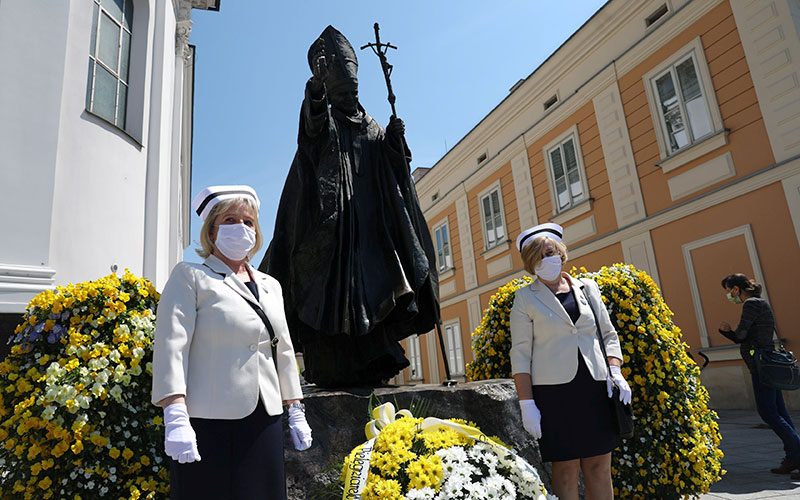 Nurses in protective masks stand in front of a statue of St. John Paul II in Wadowice, Poland, May 18, 2020, during a ceremony to commemorate the 100th anniversary of the late pope's birth.
