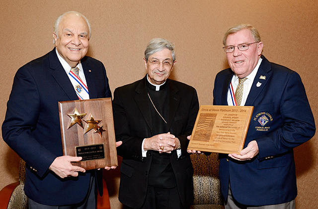 Vito Vitelli (left), Grand Knight of Knights of Columbus Council #15471, and Tucker Wilson (right), past Grand Knight, pose with Bishop Salvatore R. Matano while holding the Triple Star Award and New York State Circle of Honor Platinum Award.