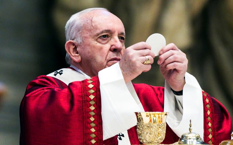 Pope francis in red celebrating mass