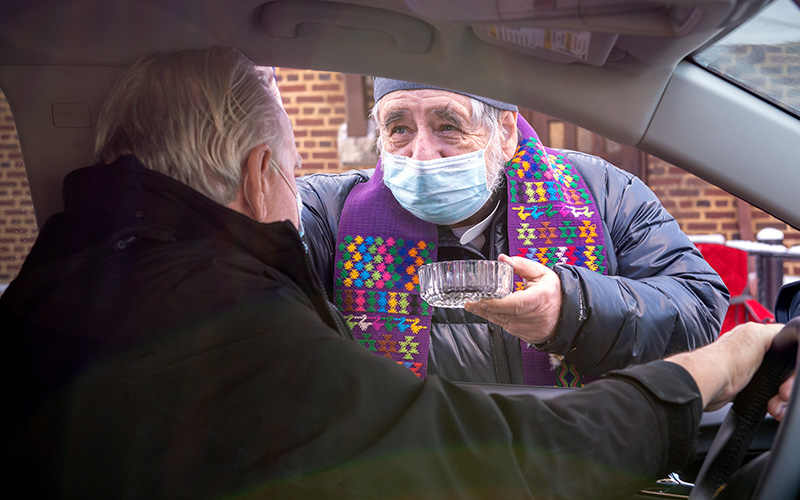 Father Raymond Fleming distributes ashes through a car window outside of Rochester's St. Monica Church Feb. 17.