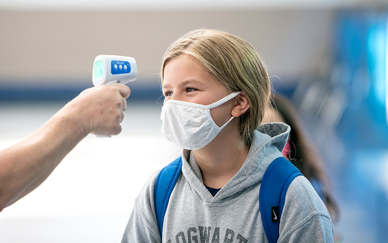 Francesca Riess has her temperature checked upon arriving at Seton Catholic School in Brighton Sept. 9. (Courier photo by Jeff Witherow)