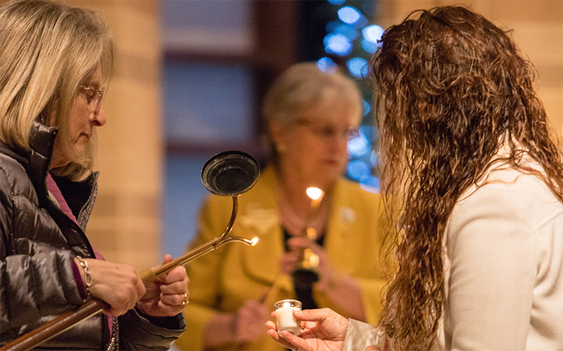 A woman lights a candle during the St. Gianna's Hope Memorial Mass for Infant Loss at Prince of Peace Catholic Church in Houston.