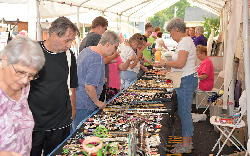 Members of the community look at items for sale in a tent outside St. Mary Church in Canandaigua during the 2019 Lawn Sale.