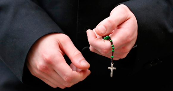 Person holding a rosary in their hands