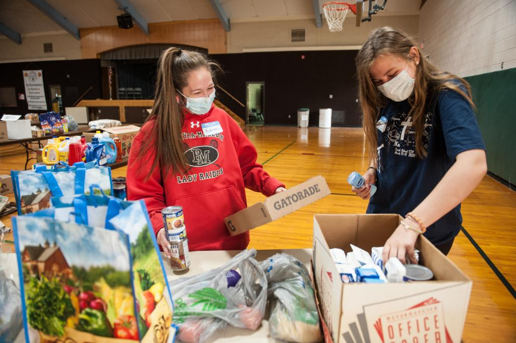 Kaleen Anderson (left) and Brigid Lang organize donations at St. John of Rochester parish during food drive June 13.