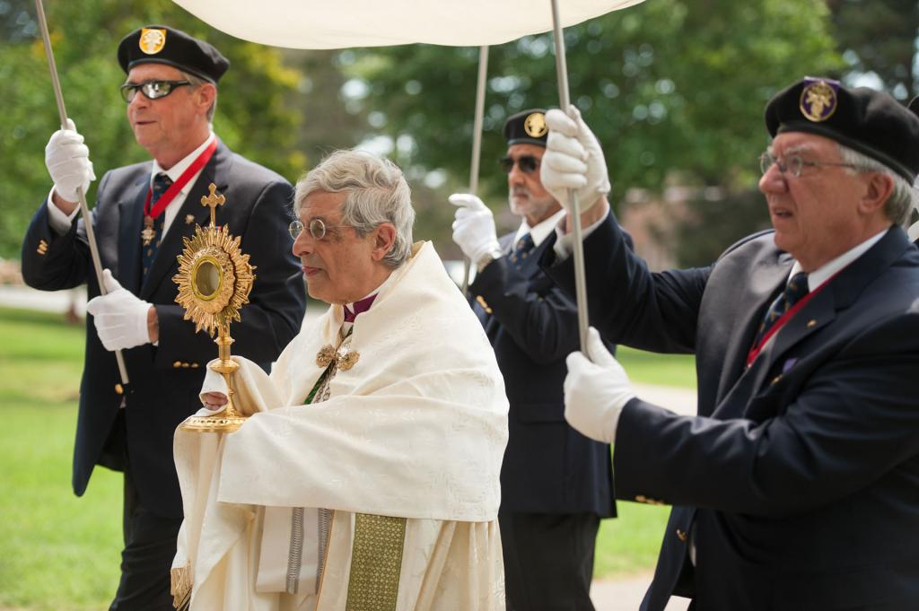 Members of the Knights of Columbus hold a canopy as Bishop Matano leads the procession.