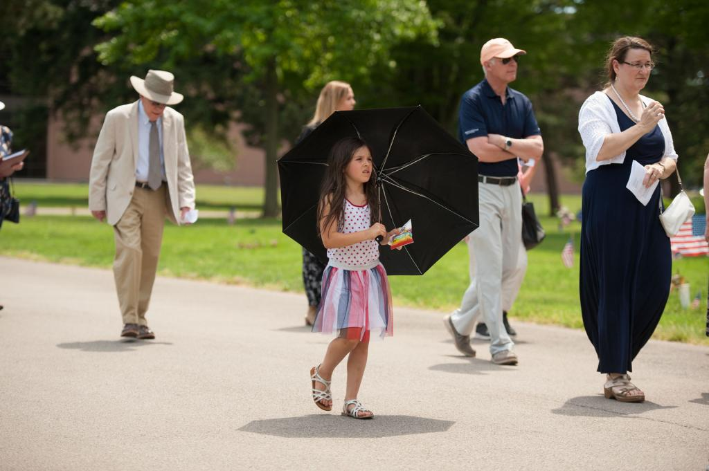 Six-year-old Elianna Neuroth shades herself from the sun during the procession.