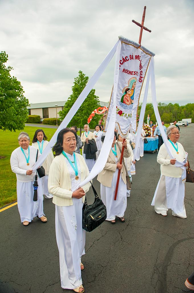 Van Vo (center nearest camera) marches during the Filipino Santacruzan procession of the rosary at St. Jude the Apostle Church in Gates May 21.