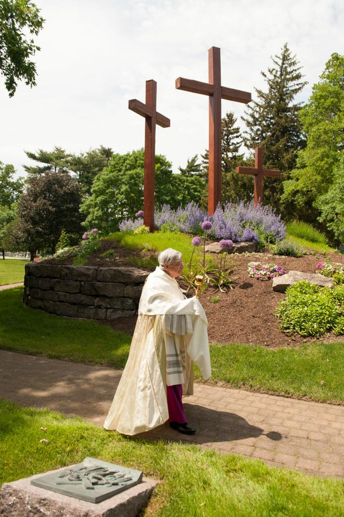 Bishop Matano processes with the monstrance past the Way of the Cross monument.