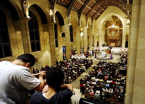 Children stand in the choir loft during the crowded Chrism Mass.