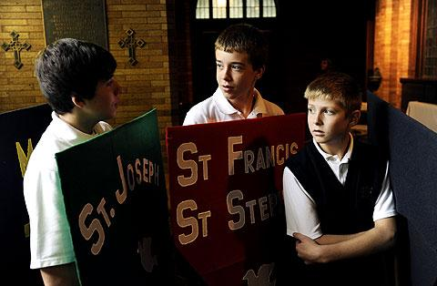 Joe Puma (L), Henry John & Ryan Quigley carry banners.