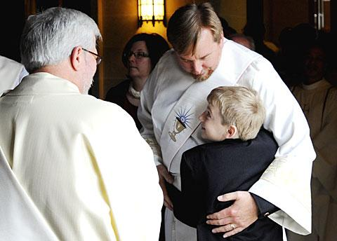 Father Caton is hugged by his son Alexander before Mass.