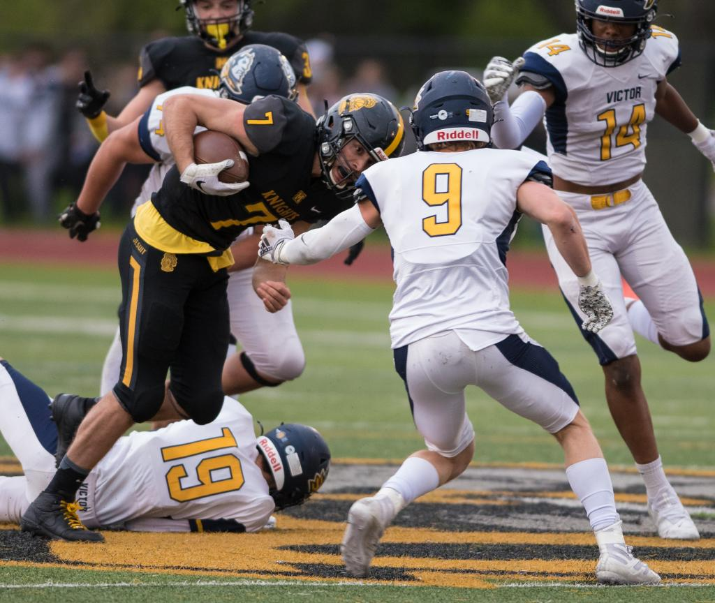 McQuaid Jesuit quarterback Joe Cairns (left) looks for a route around Victor's Trevor Knapp during the Section 5 Class AA football championship at McQuaid Jesuit May 1.