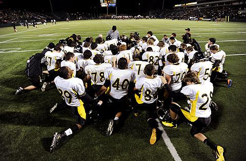 McQuaid players join in prayer before the game.