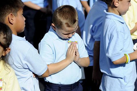 Second-grader Christian Sharpstene prays.