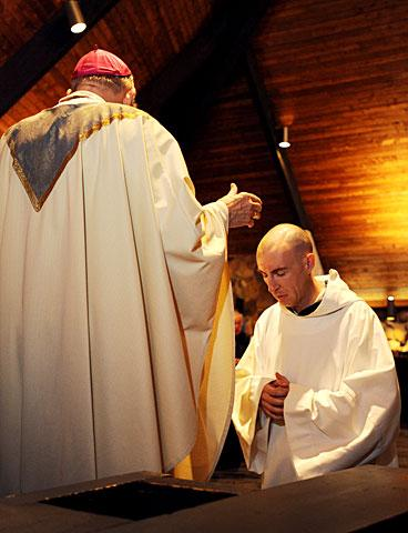 Brother Slater kneels before Bishop Clark.