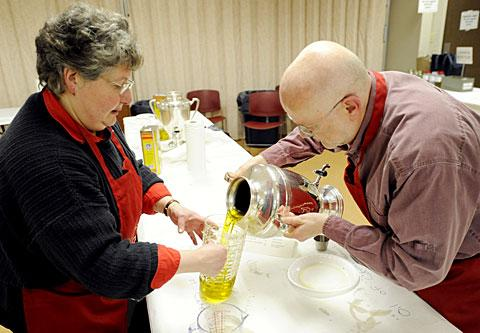 Marianne Himmelsbach and Gene Cherkis distribute oils.