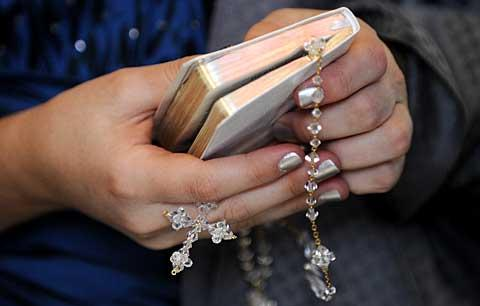 Natalie holds a Bible and rosary during the Mass.