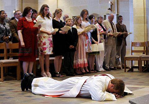 Father Caton prostrates himself as his family looks on.