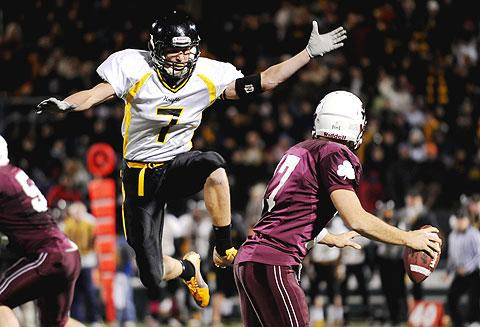 McQuaid's Jordan Ghyzel leaps toward Cory Benedetto.